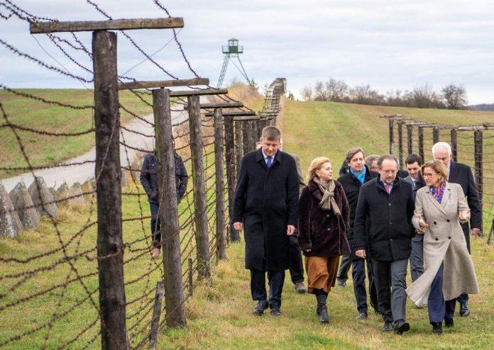 Außenminister Alexander Schallenberg und Landeshauptfrau Johanna Mikl-Leitner sowie weitere Teilnehmerinnen und Teilnehmer der Gedenkveranstaltung besichtigen die Reste des einstigen Eisernen Vorhangs bei Cizov