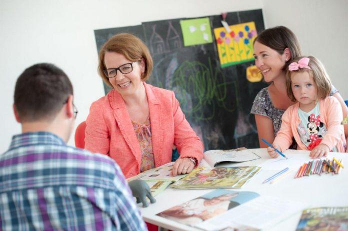 Familien-Landesrätin Christiane Teschl-Hofmeister spricht mit einer Familie über Ferienbetreuung